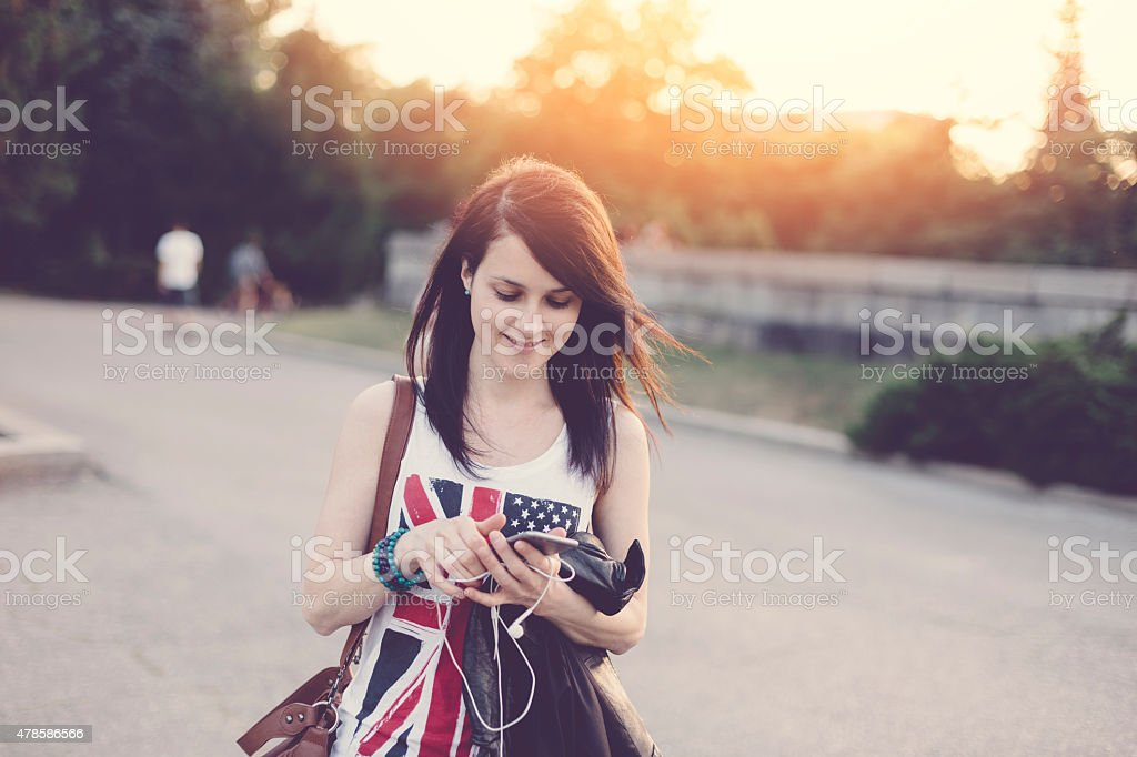 Girl texting on smarthone in the city stock photo