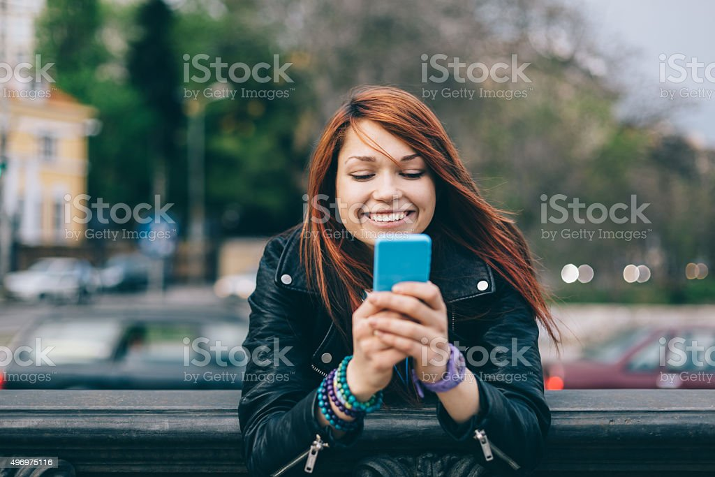 Girl texting on smartphone at the street stock photo