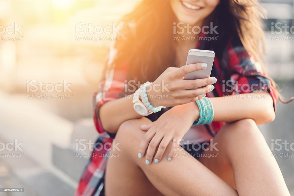 Girl texting on smartphone outside stock photo