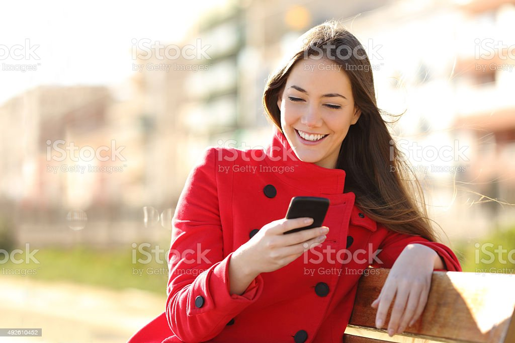 Girl texting on the smart phone sitting in a park stock photo