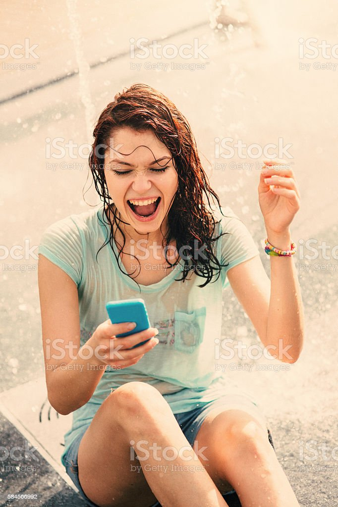 Girl texting under a fountain stock photo
