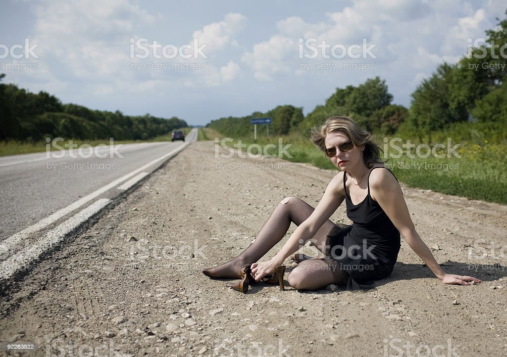 girl - the prostitute sits on a roadside of road stock photo