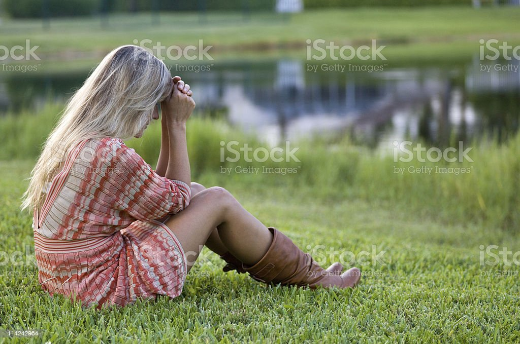 A girl thinking of something at the river with no hope royalty-free stock photo