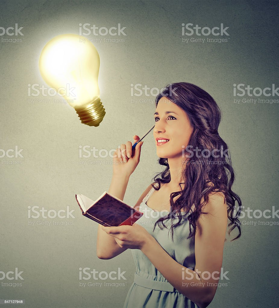 girl thinking planning looking up at bright light bulb stock photo