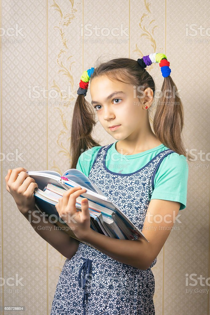 girl thoughtfully standing with a stack of books stock photo