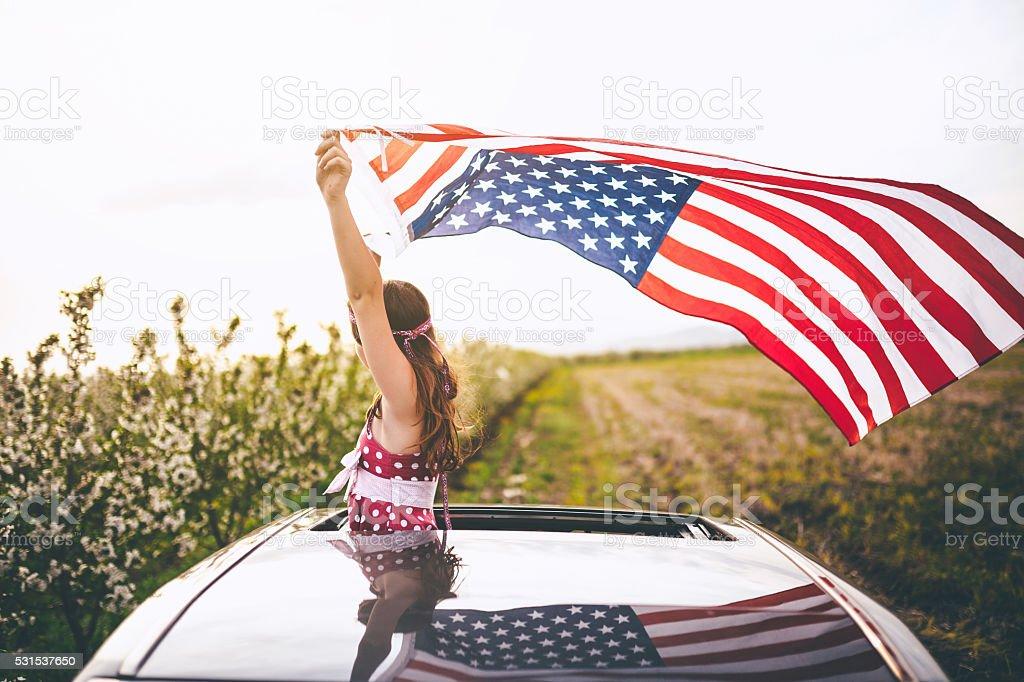 Girl Through a Car Sunroof Waving with USA Flag stock photo