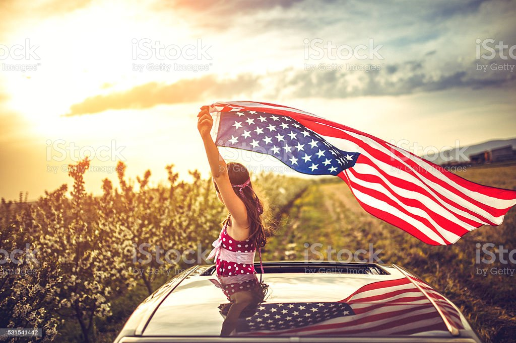 Girl Through a Car Sunroof Waving with USA Flag stock photo
