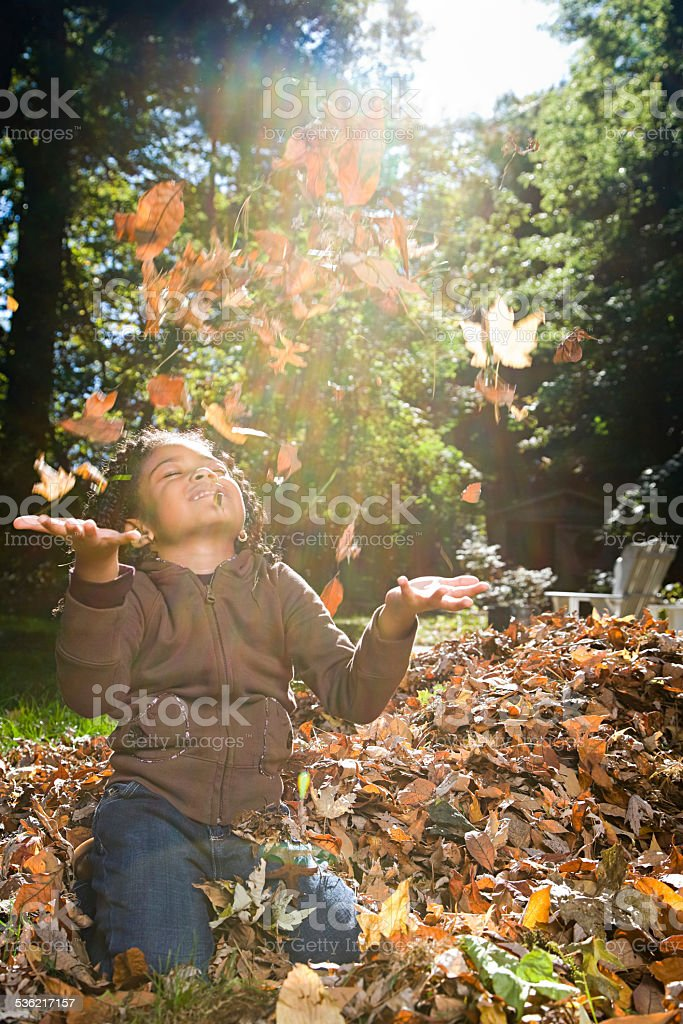 Girl throwing leaves stock photo
