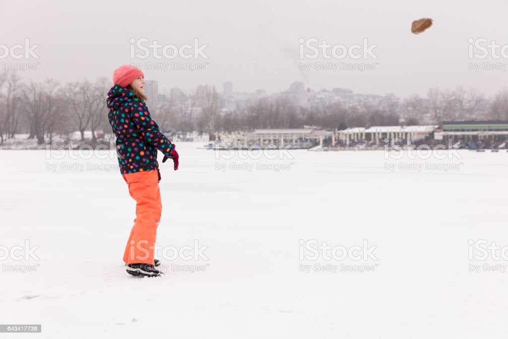 Girl throwing stone on frozen lake stock photo