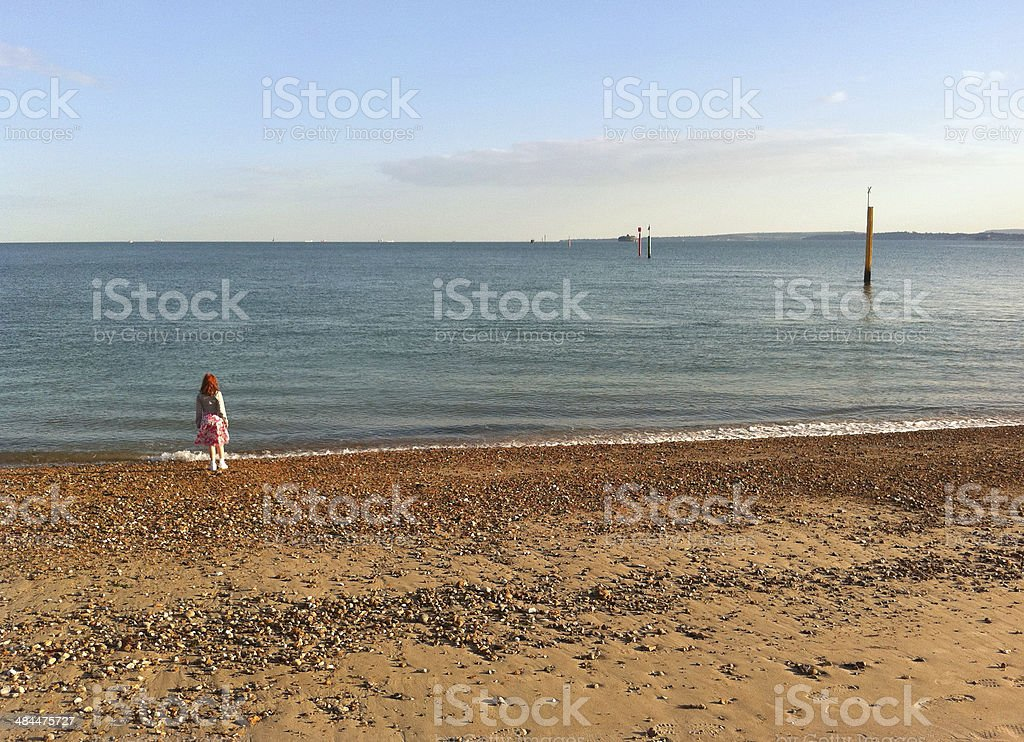 Girl throwing stones into sea on Portsmouth beach, England, UK stock photo