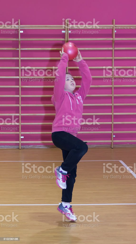 Girl throws a ball in the basket stock photo