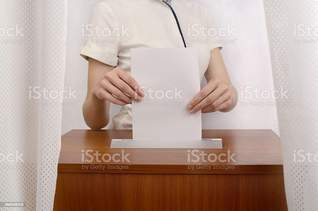 Girl throws a ballot into the box stock photo
