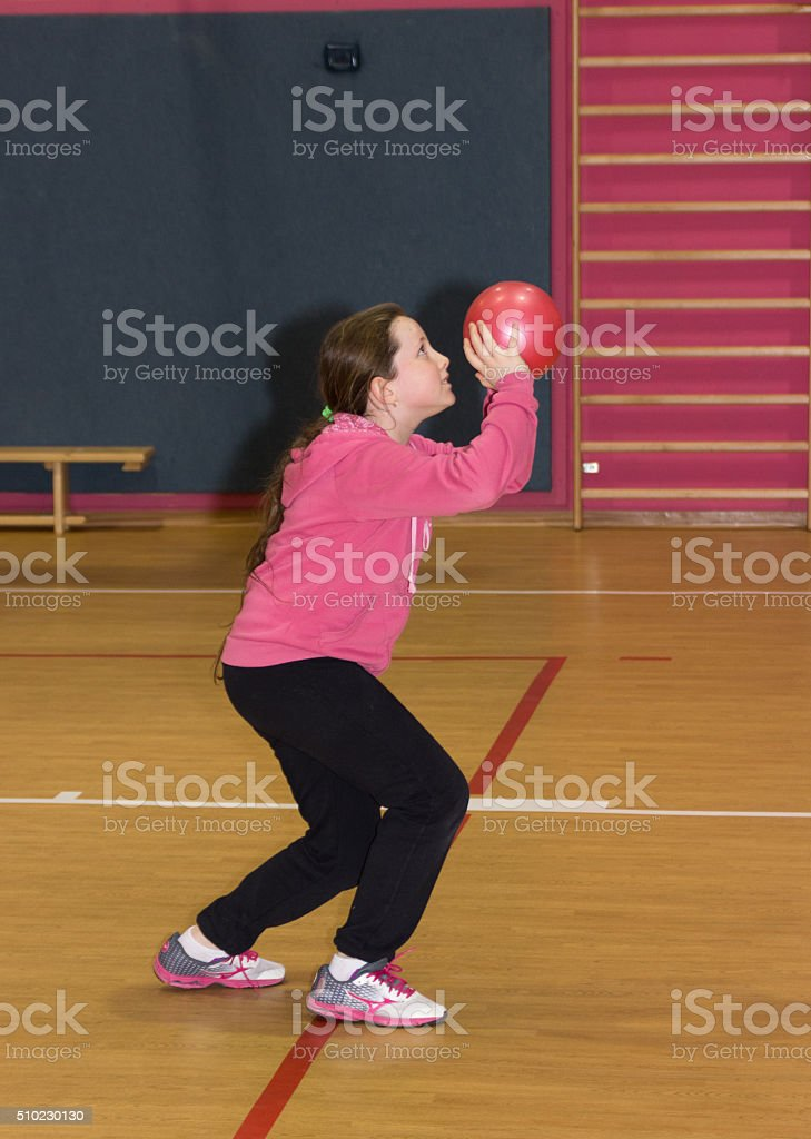 Girl throws a red ball in the basket stock photo