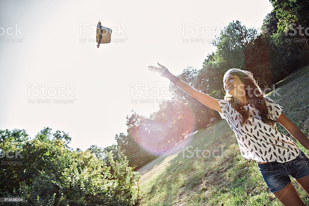Girl throws hat in air stock photo