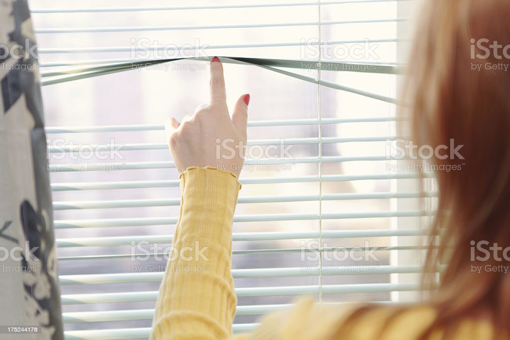 Girl touches blinds. royalty-free stock photo