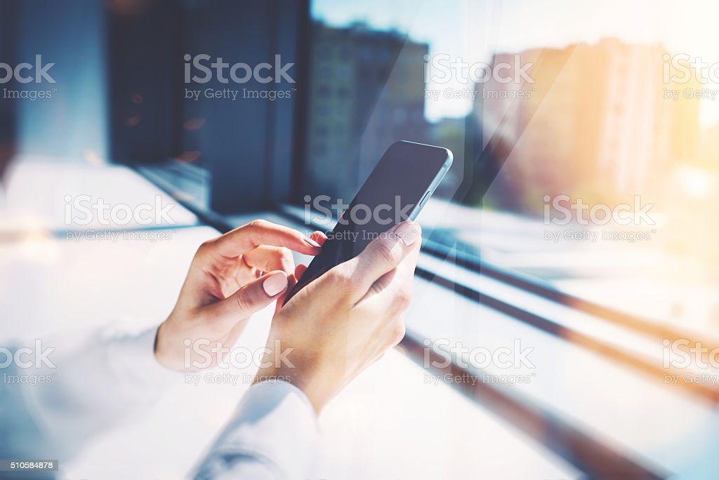 Girl touching a screen of her smarthone. Blurred background, horizontal stock photo