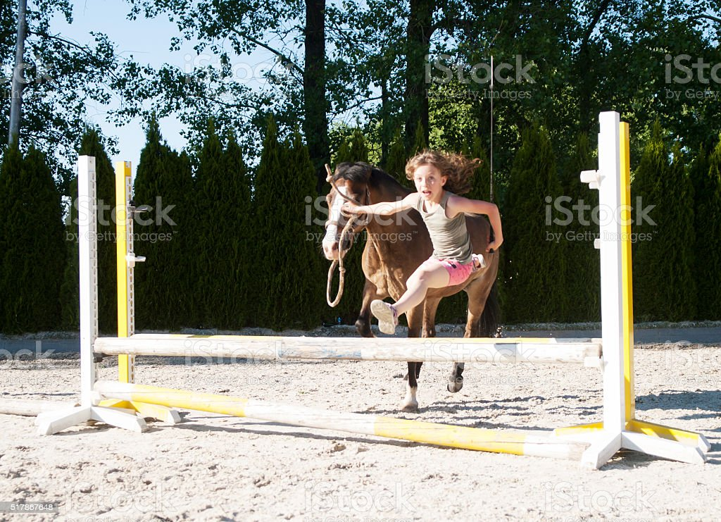 Girl training jumping with pony stock photo