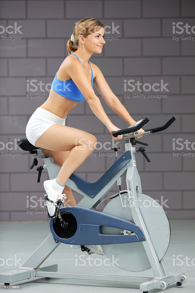 Girl training on exercise bike at the gym royalty-free stock photo