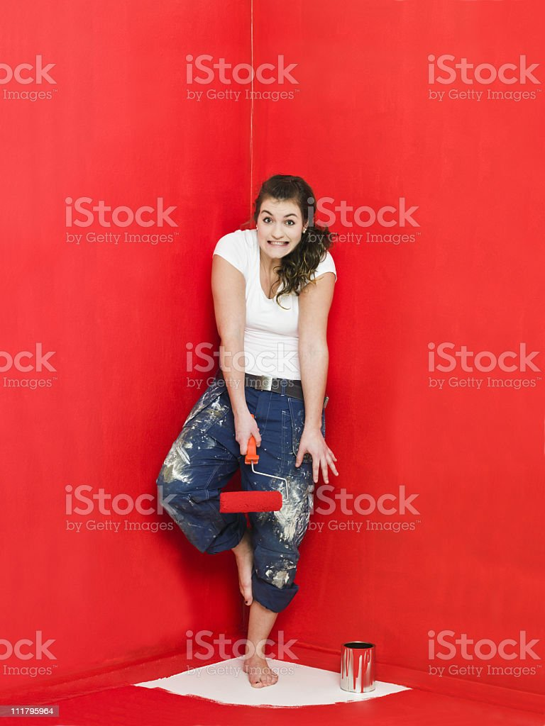 Girl trapped in a corner while painting room red royalty-free stock photo