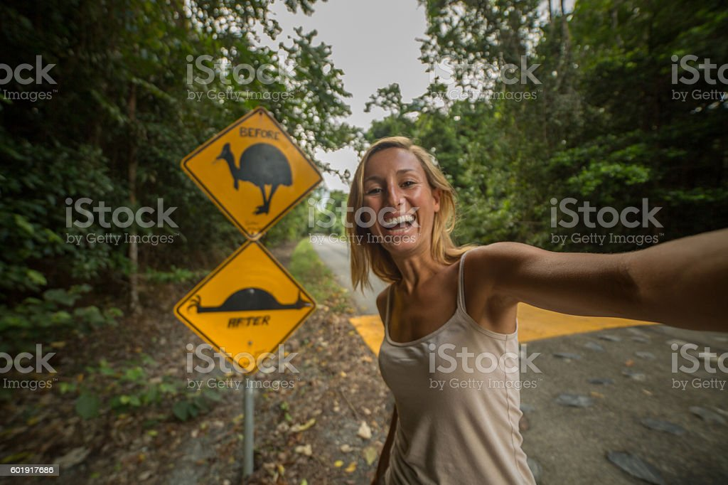 Girl traveling takes selfie with humorous cassowary road sign stock photo