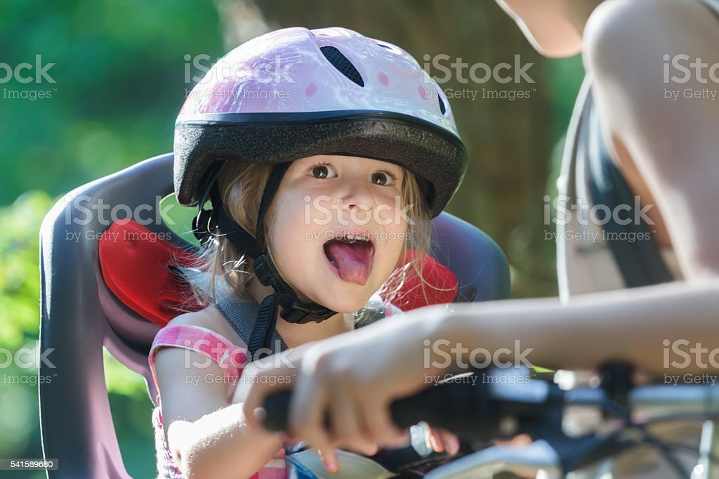 Girl travelling on child seat and sticking tongue out stock photo