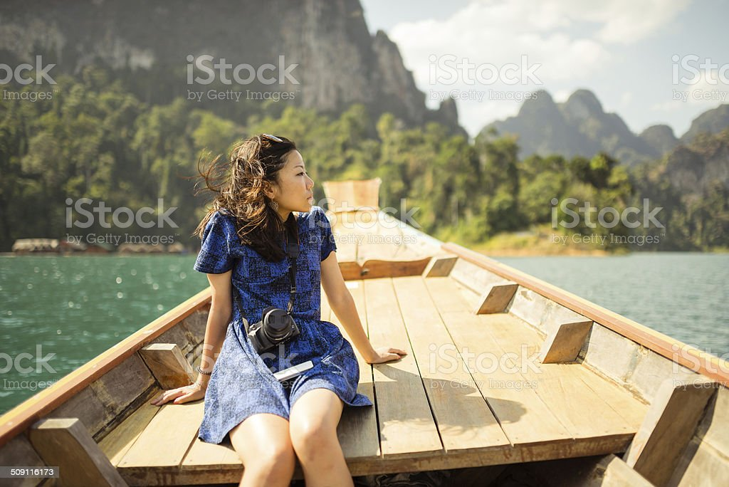 Girl travelling on long tail motorboat stock photo