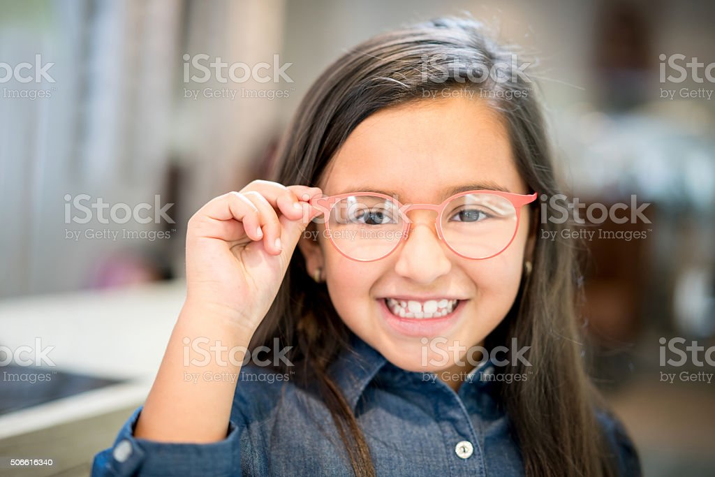 Girl trying glasses at the optician stock photo