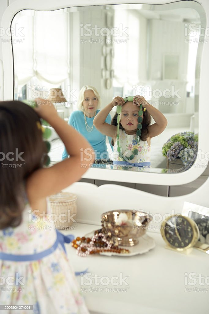 Girl (2-4) trying on necklace in mirror, grandmother in background royalty-free stock photo