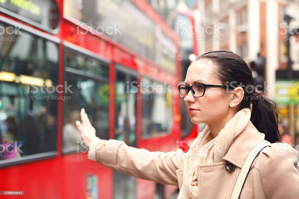 Girl trying to catch a taxi in London stock photo