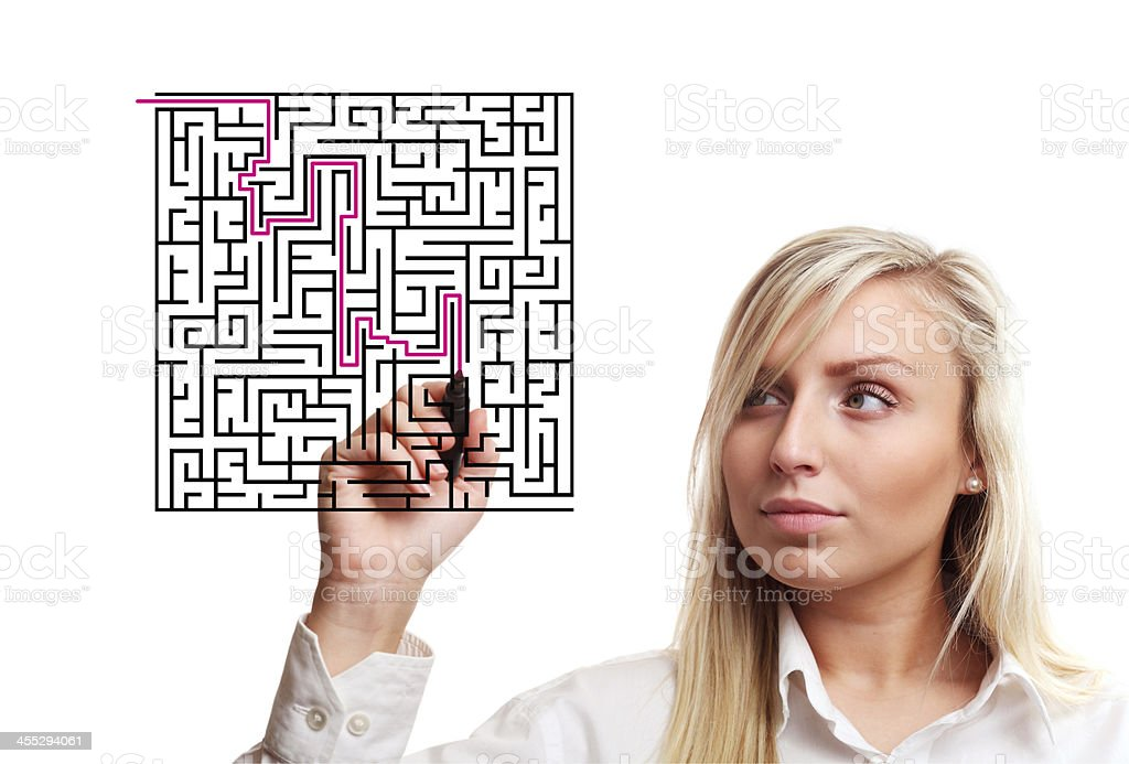 Girl trying to find way through labyrinth stock photo