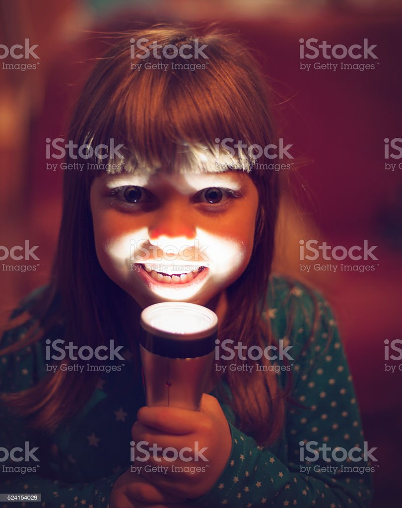 Girl trying to scare someone with flash light stock photo