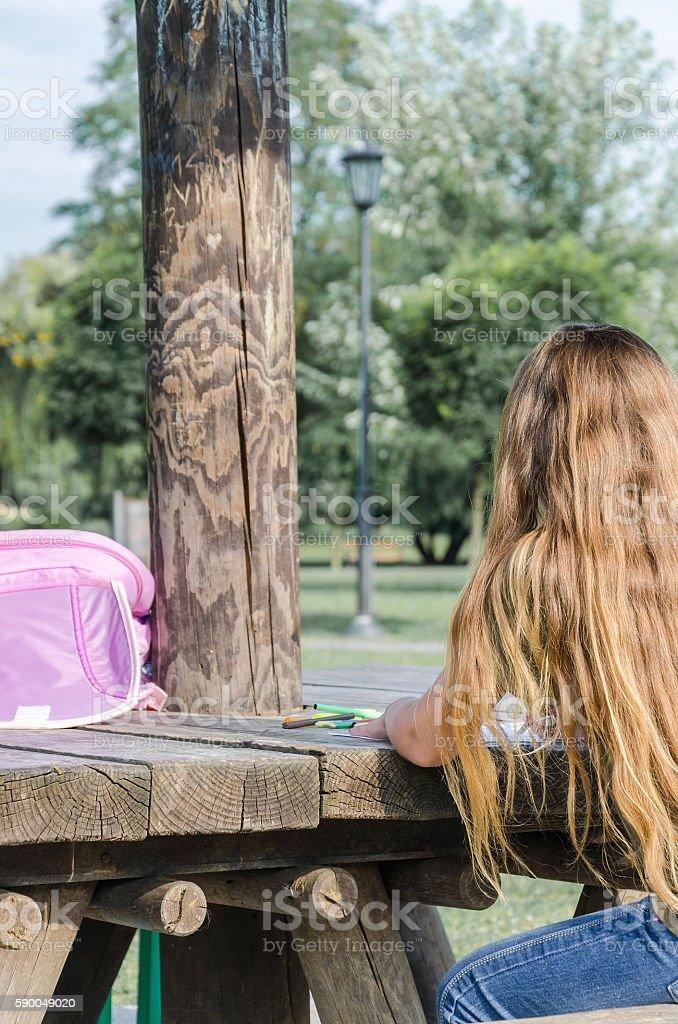 Girl turned back in the schoolyard written homework stock photo