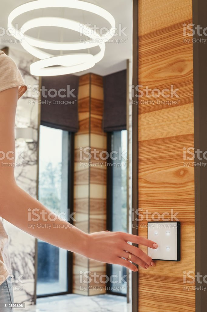 girl turns on the light presses on the touch switch stock photo