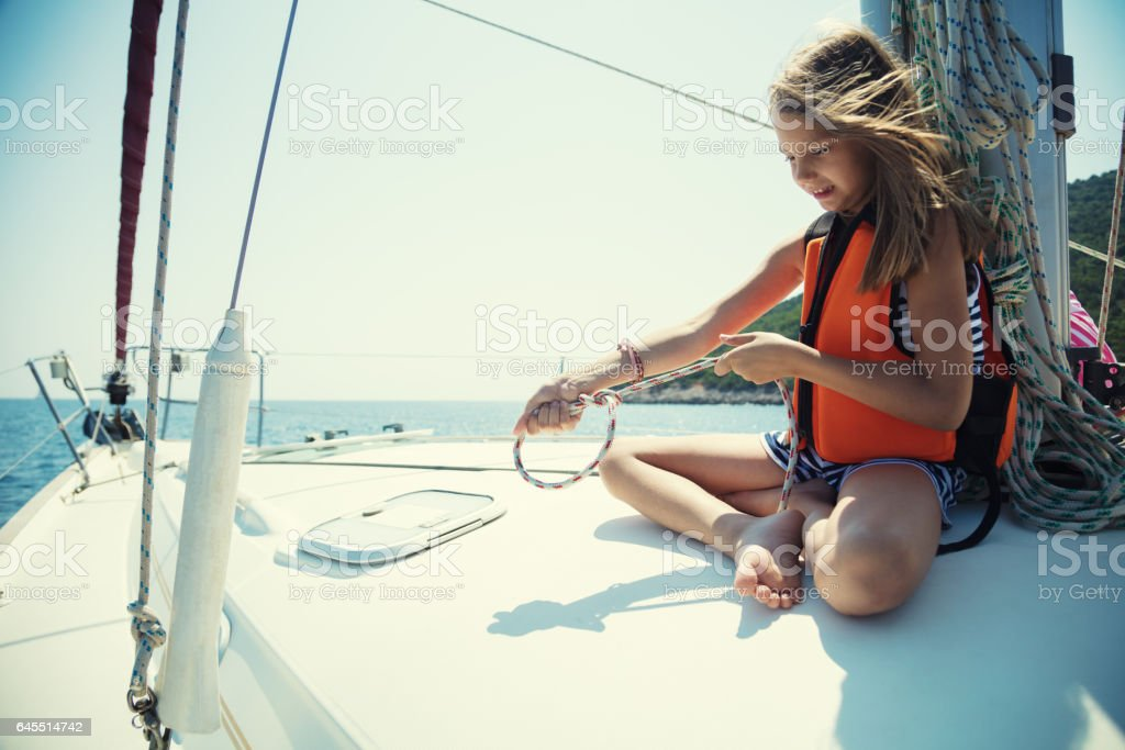 Girl tying knots on vacation on sailboat stock photo