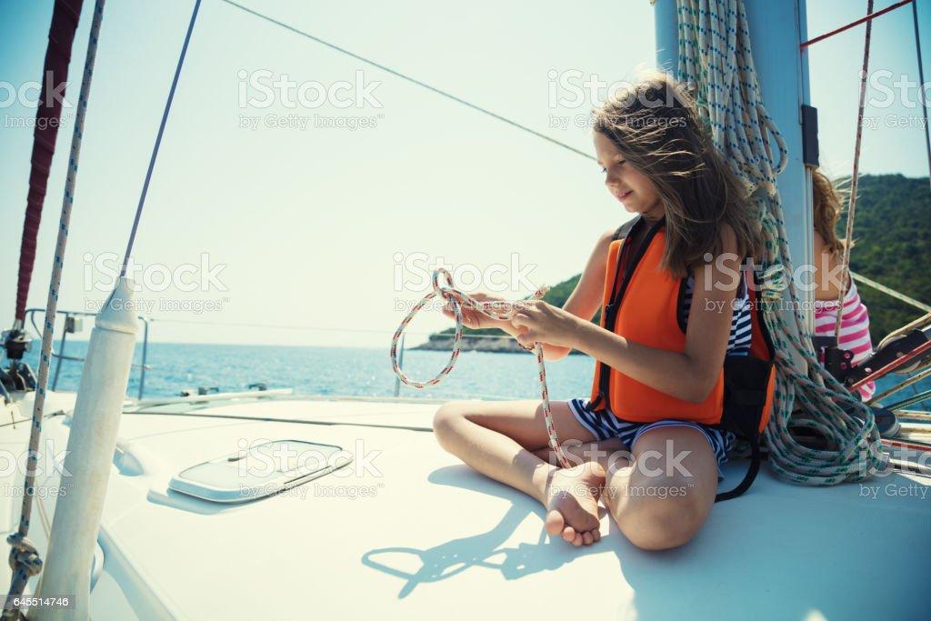 Girl tying knots on vacation on sailboat stock photo