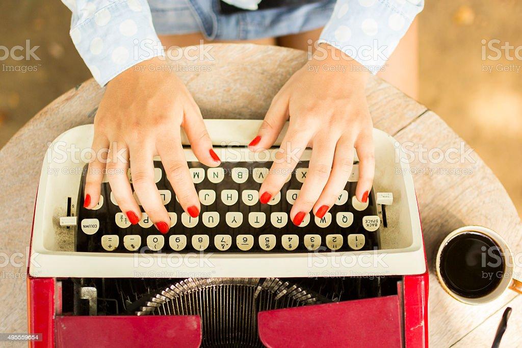 Girl typing on the old typewriter stock photo