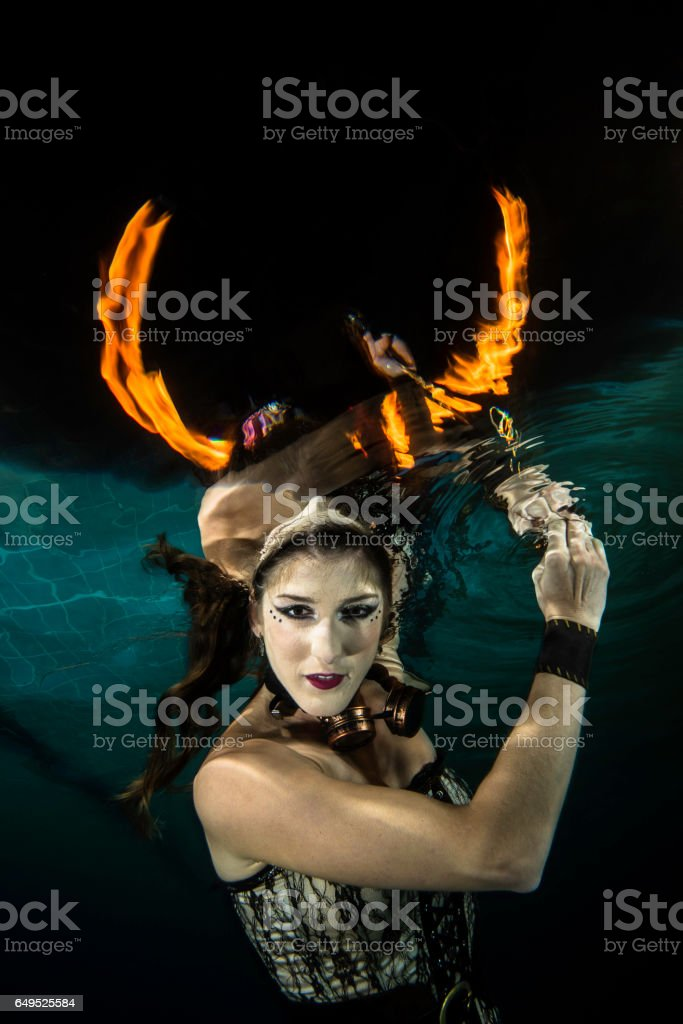 Girl underwater with firehorn stock photo
