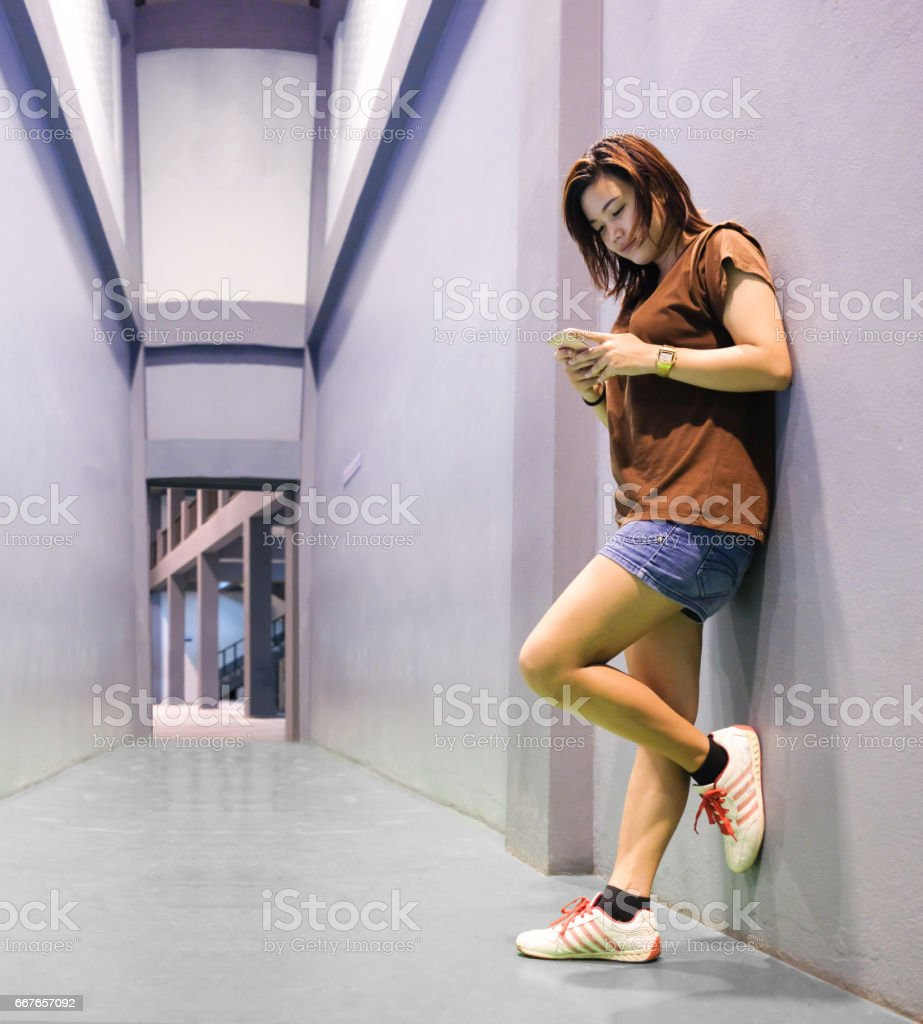 Girl use smartphone while relax from exercise with perspective background stock photo