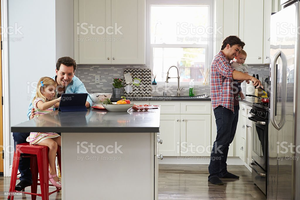 Girl uses tablet in kitchen with dad, while other dad cooks stock photo