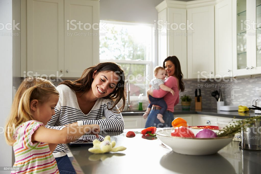 Girl uses tablet in kitchen with mum, other mum holding baby stock photo
