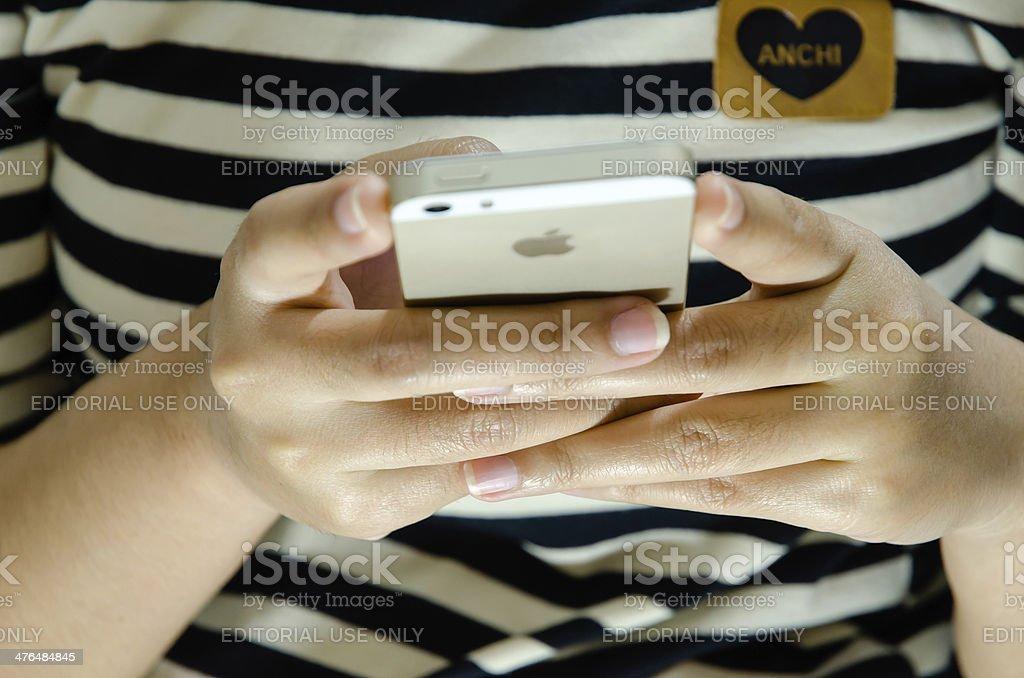 Girl using  an iPhone 5s. Close-up shot stock photo