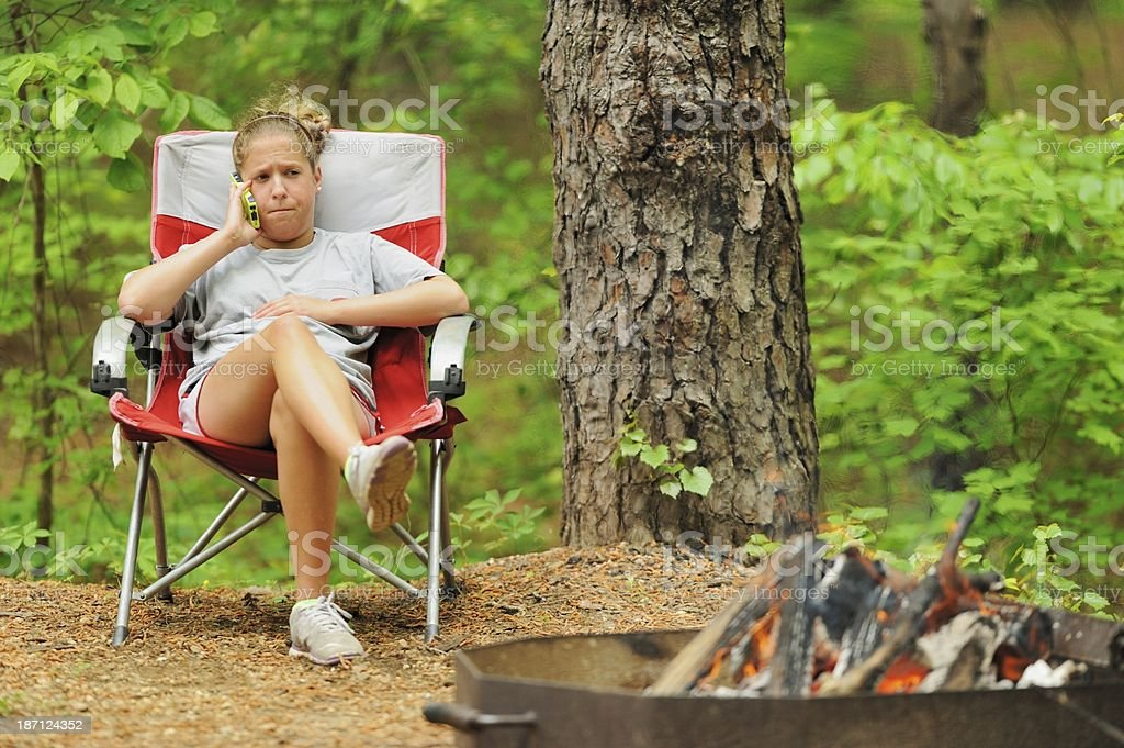 Girl using cell phone by campfire royalty-free stock photo