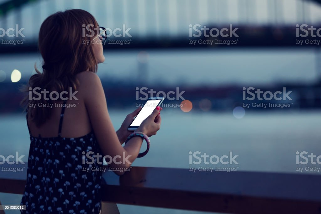 Girl using cellphone in city / urban surroundings - near river. Focus is on the phone. stock photo