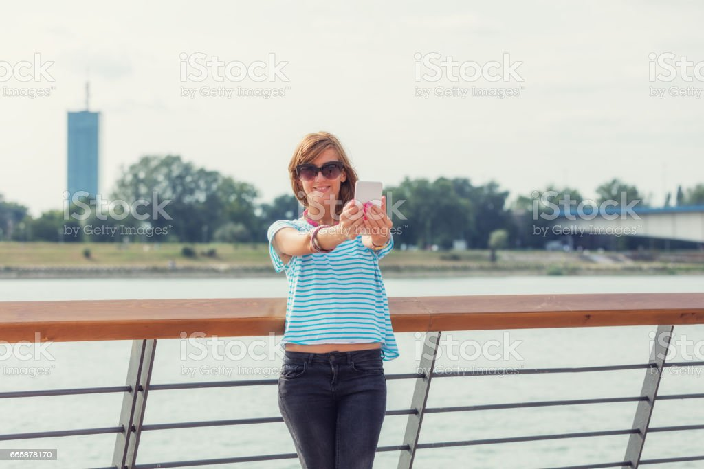 Girl using cellphone on the pier near the river. stock photo