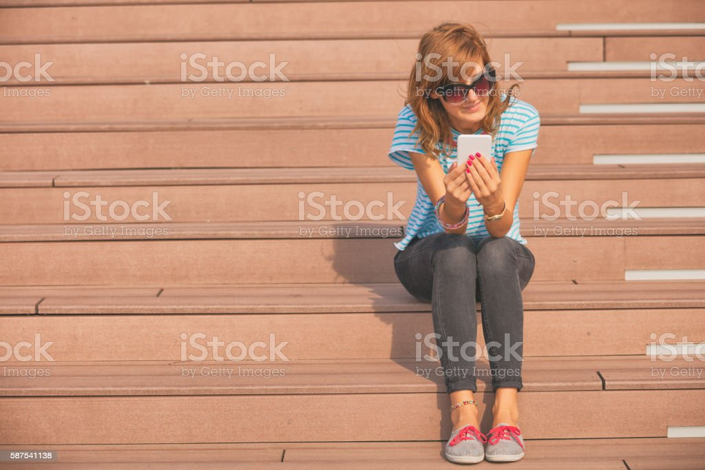 Girl using cellphone outdoors. stock photo