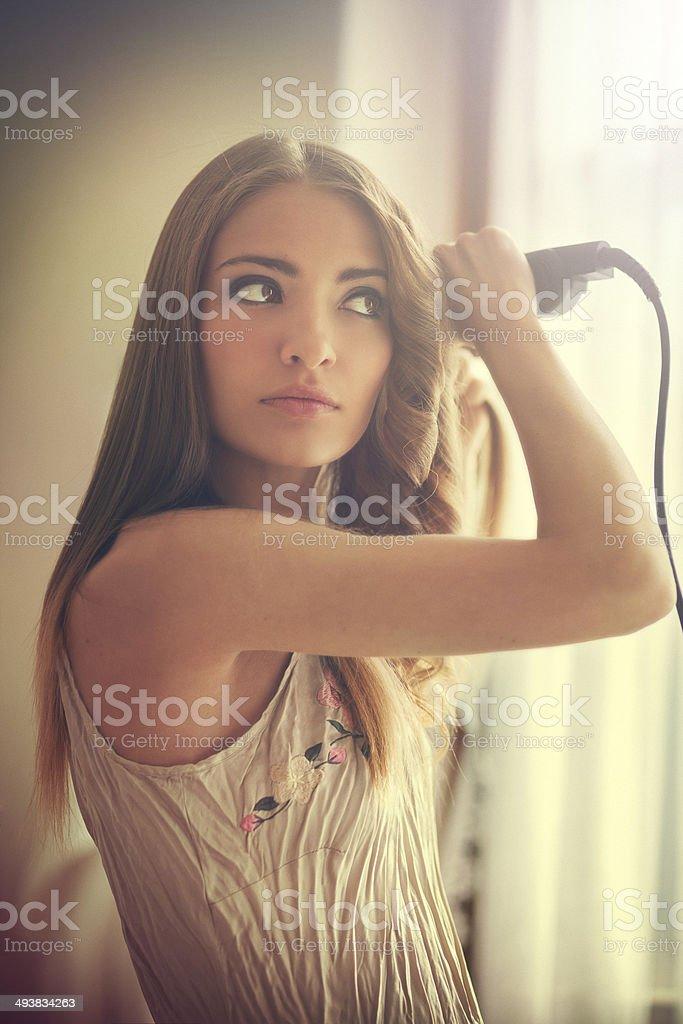 girl using curling iron stock photo