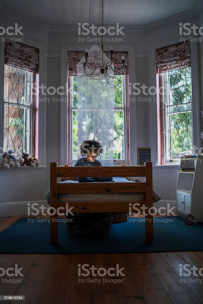 Girl using digital tablet on bed stock photo