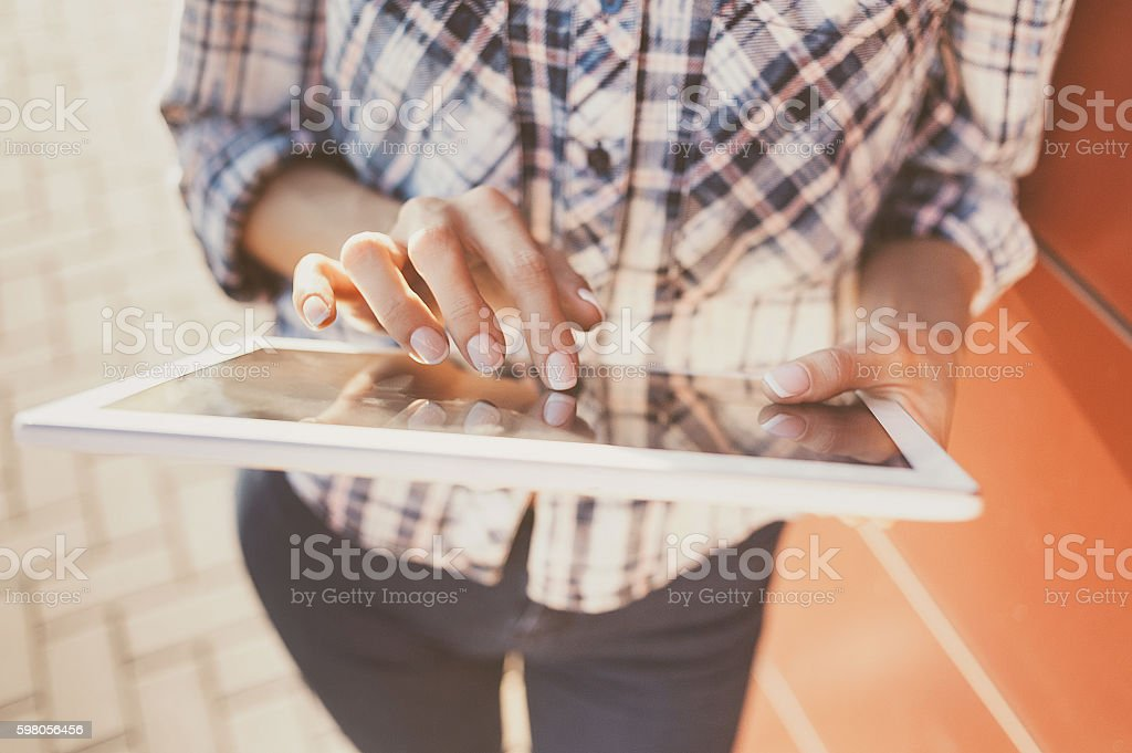 Girl using digital tablet outdoors stock photo