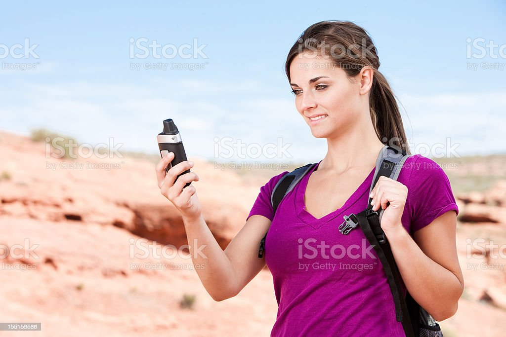 Girl Using GPS Device in Desert stock photo