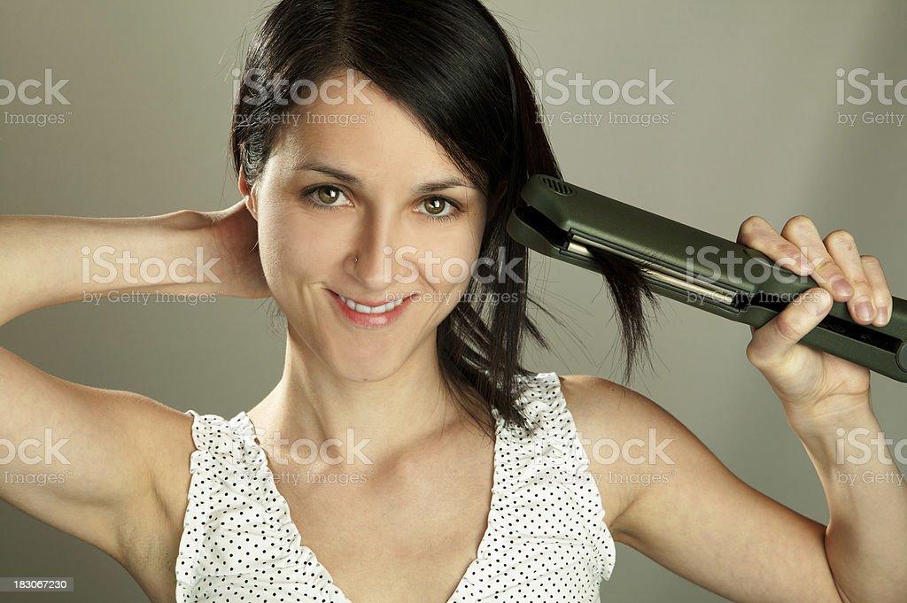 Girl using hair straightener royalty-free stock photo
